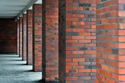 Architectural composition. Many red brick square columns in perspective.