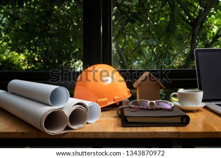 Architectural concept. Architects house model with blueprint and helmet on architect desk. #1343870972