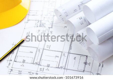 Architectural construction plans with pencil and hardhat on it