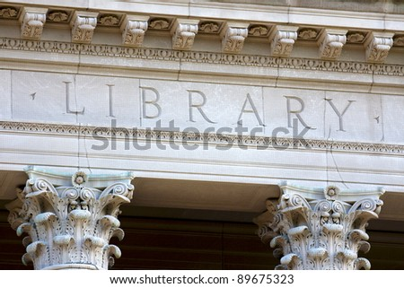 Architectural detail of a university library building, showing the letters LIBRARY chiseled into its limestone.