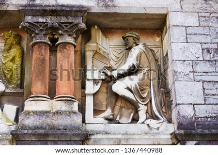 Architectural detail of statue of organist on the facade of Plymouth Guildhall building  #1367440988