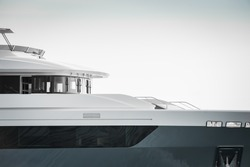 Architectural detail of the bow of a brand new superyacht, with guest cabin windows and bridge, monochromatic