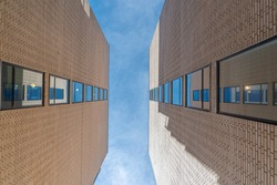 Architectural detail of two twin red brick buildings seen from below with blue sky and feathery clouds