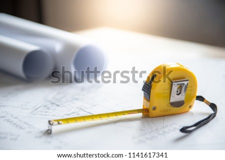 Architectural drawing plan of house project, blueprint rolls and yellow tape measure (measuring tape) on working table, Architecture and building construction industry concepts