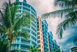 Architectural flat building Miami Style South Beach Florida image retro filtered  Modern art deco condominium construction aqua and apricot color with palm trees against blue tropical sky background