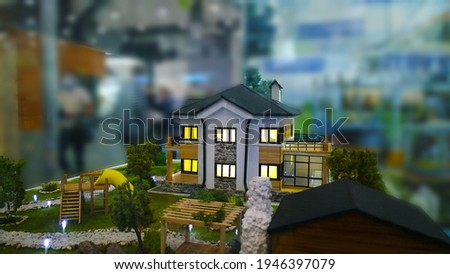 Architectural model of luxury cottage with light in windows on suburban Real estate exhibition. Green House Maquette. Mortgage concept. Healthy countryside living. Expo blur background. Energy saving. Photo stock ©