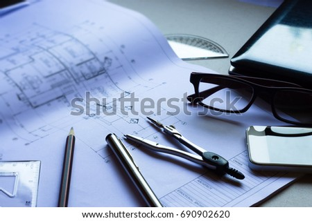 Architectural plan,Divider,pencil,pen,ruler, glasses and smartphone and blueprint on table top.Top view of Engineers table at office workplace.selective focus.Engineering house drawings and blueprint.