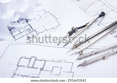 Architectural project, blueprints, blueprint rolls and divider compass, calipers on plans Engineering tools view from the top. Copy space. Construction background.
