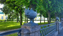 Architectural sculptural forms in the form of mythical animals on a metal and concrete fence. Ancient  fencing in the old garden. Sights and beautiful places in St. Petersburg, Russia.