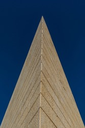 Architectural structure in the form of a pyramid, lined with tiled stone, against a blue sky