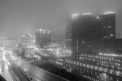 Architectural view of skyline above streets and river and cityscape of  Chicago effect at night on foggy evening in Illinois, USA.