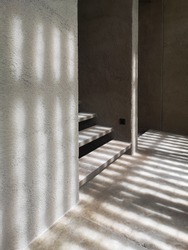 Architecture and Exteriors : Burred light and shadow passing through window in the building of hotel. Beautiful morning light shine in the concrete wall make shadow on stairway and the floor