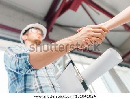 architecture and home renovation concept - builder with blueprint shaking partner hand #151041824