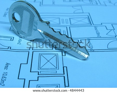 Architecture and real estate concept: House key on a house plan (Blue tone)