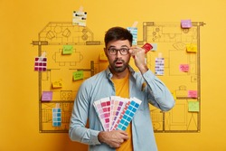 Architecture and renovation concept. Stupefied bearded man holds color palette and paint brush, keeps hand on rim of glasses, stands against house sketch with sticky notes, works on remodeling
