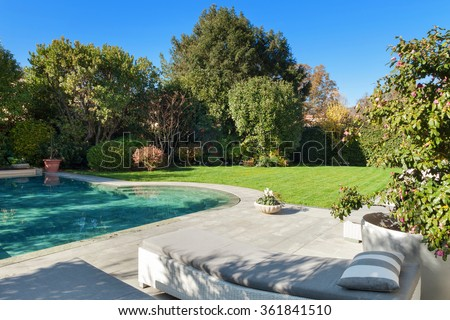 Architecture; beautiful garden with pool, two sunbeds view