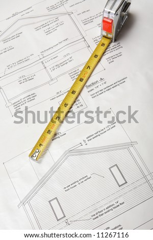 Architecture blueprints of home addition with tape measure