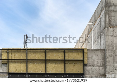 Architecture concept. Element of modern building under construction with rock wool insulation on exterior and copy space on concrete wall, against blue sky on background