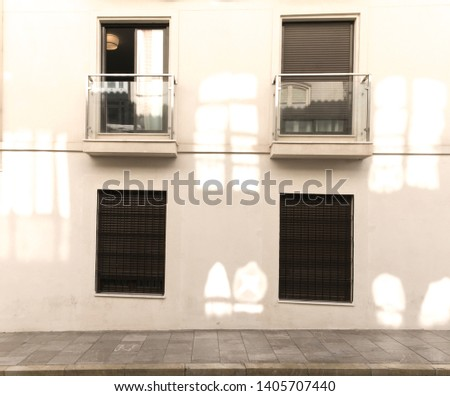Architecture exterior facade view of modern office building wall with lights and shadows. Modern urban architecture with four windows, two opened, two closed, two balconies. #1405707440