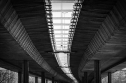Architecture lines under the bridge with concrete poles and reinforcement protecting the bridge from collapsing black and white, transportation industry concept