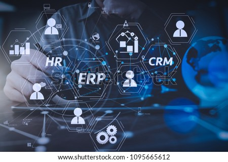 Architecture of ERP (Enterprise Resource Planning) system with connections between business intelligence (BI), production, CRM modules and HR diagram.businessman hand working with modern digital table