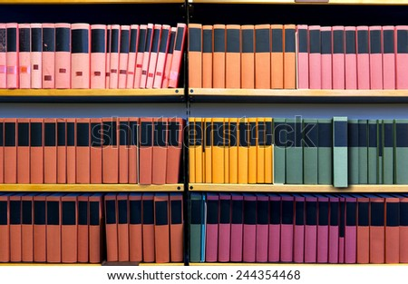 Archive with many binders on shelf, one file pulled out.