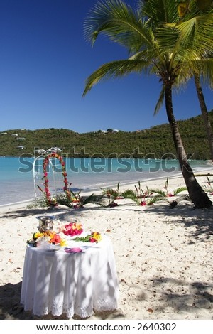 Archway and table decorated with flowers and fruits on a caribbean beach - stock photo