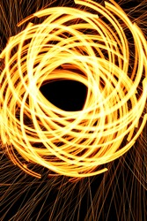 Arcs of fire, created by spinning steel wool that is set on fire.