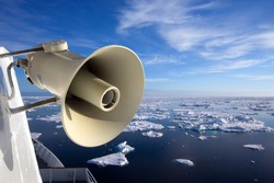 Arctic ice melt bullhorn global warming alert message. A megaphone bullhorn on an ice breaking ship with melting arctic ice in the sea, symbolic of broadcasting the message of global warming