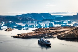 Arctic landscape, top view on icebergs , mountains and expedition cruise ship, Umanaq Bay, Greenland