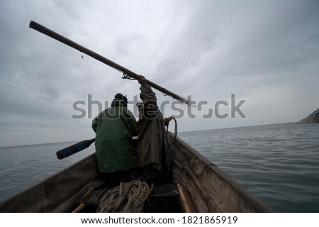 Arctic sea hunters hunt walruses and seals in the Bering Strait. Traditional Chukchi sea animal hunting using a harpoon. Severe northern nature. Vicinity of Cape Dezhnev, Chukotka, Far East of Russia.