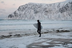 Arctic surfer going by beach after surfing