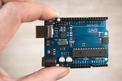 Arduino Uno board electronics in hand for programming the microcontroller