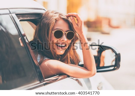 Are you going with me? Rear view of beautiful young cheerful women looking at camera with smile while sitting in her car  Foto stock ©