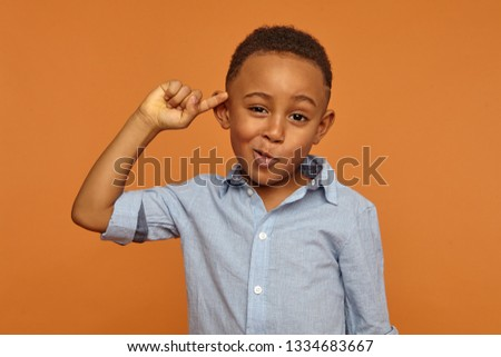 Are you out of your mind? Horizontal shot of handsome emotional Afro American little boy in shirt twisting fore finger at his temple. making fun of crazy idea. Body language, signs and gestures