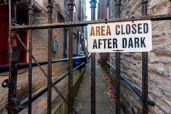 Area Closed After Dark sign on metal plate is attached to the metal railings of a door in front of a vintage passageway at an urban location. A narrow alley is seen in blurred background behind fence.