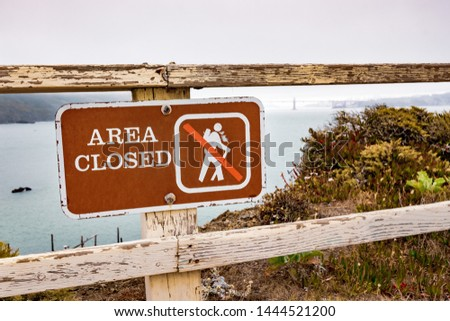 Area Closed sign posted on the Pacific Ocean coast in Marin Headlands, Marin County; Golden Gate Bridge engulfed by fog visible in the background; San Francisco, California #1444521200