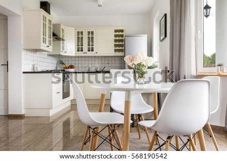 Area of dining room with table and view of the bright open plan kitchen