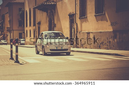 AREZZO, ITALY - JUNE 26, 2015: The newest version of Fiat 500, one of the most popular small city cars in Italy, on cross roads in tuscan Arezzo city, Italy