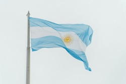 Argentina flag blowing in the wind, with sky background. Blue and white flag with golden sun. Shot in Buenos Aires.