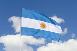 Argentina flag isolated on the blue sky with clipping path. close up waving flag of Argentina. flag symbols of Argentina.