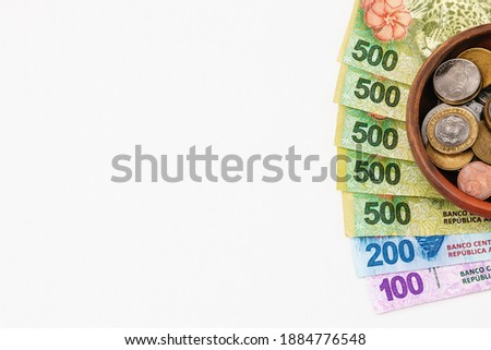 Argentine pesos 500, 200 and 100 Bills arranged in fan shape on a white background under a clay bowl with Argentine peso coins and a 2 cvs US dollar coin. BANK REPUBLIC leyend in the bills Photo stock ©