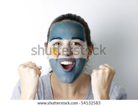 Argentinean fan screaming GOAL with hands up and painted flag on her face.