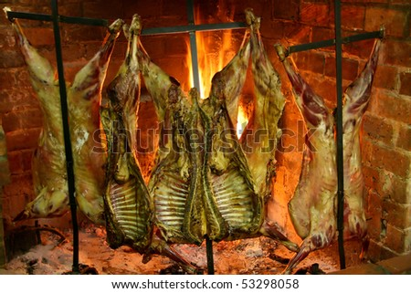 Argentinian Barbecue - Sheep roasting near a fire in a typical Parilla restaurant in Patagonia.