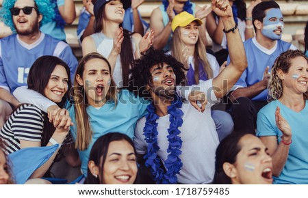 Argentinian spectators in stadium cheering their national football team. People from Argentina in fan zone cheering for their soccer team.