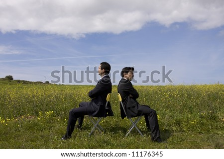 argue between two businessman in a field