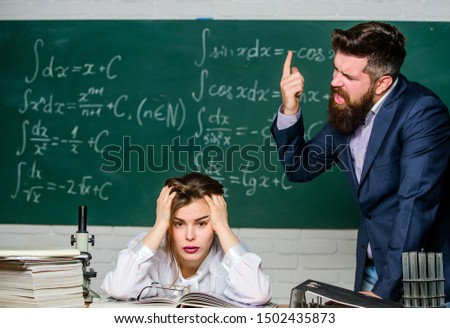 Arguing about study. Conflict situation. School conflict. Demanding lecturer. Teacher strict serious bearded man having conflict with student girl. Rebuke and punishment. You should make more efforts. #1502435873