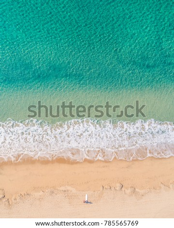 Arial drone shot of surfer on the beach with tropical water and white wash #785565769
