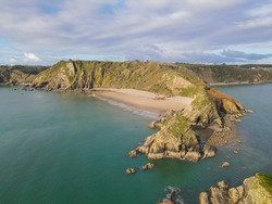 Ariel view from out at sea of Monkstone Beach, Pembrokeshire, Wales, UK. A remote, small sandy beach that is surrounded by cliffs which has excellent views and stunning coastal waters.