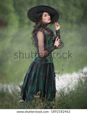 Aristocratic dark-haired lady in a green dress on the shore of a pond